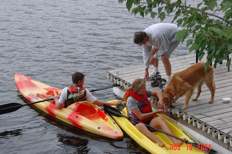kids kayaking with dog and dad